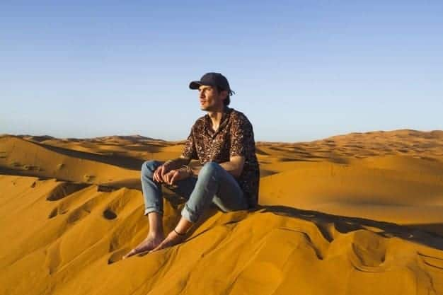 man sitting top dune desert 23 2148194012 - Guide Morocco Tours | Morocco Guided Tour